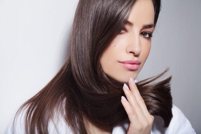 kobieta trzymająca zdrowe i lśniące włosy